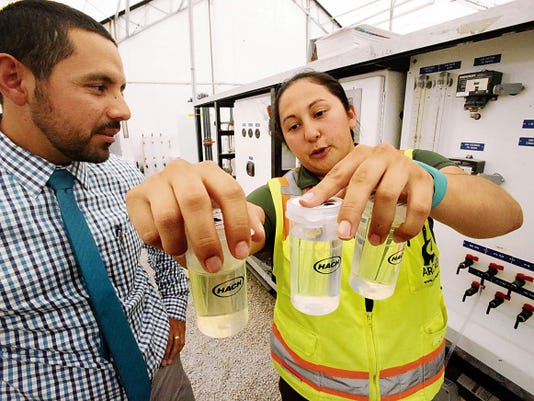 Chelsea Francis, right, water resources specialist with Arcadis U.S. Inc., shows Gilbert Trejo, chief technical officer with El Paso Water Utilities, three water samples taken at different stages in the purification process at a pilot advanced water purification plant next to the Bustamante Wastewater Treatment Plant in El Paso's Lower Valley on Wednesday.