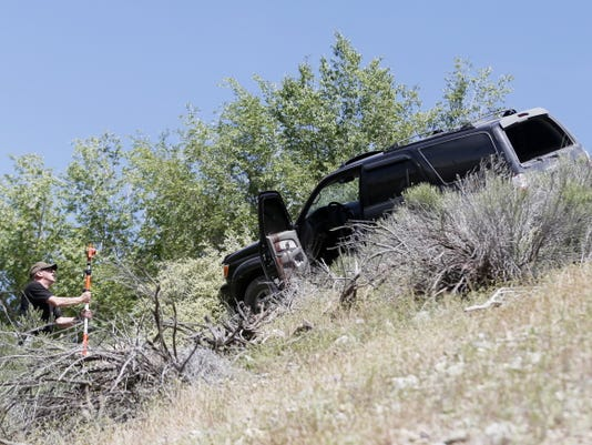 A San Juan County Sheriff's Office deputy takes measurements, Monday, off Bluff Road in Shiprock, N.M., at a crime scene next to the SUV involved in a chase that ended in Shiprock.