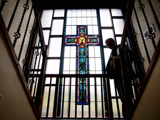 "Jairo Martinez walks past a stained glass window depicting a cross after hosting a radio program for the Latino Catholic community at the Archdiocese of Atlanta studio ""Nuestra Fe"" in Lilburn, Ga., on Thursday, Aug. 13, 2015."