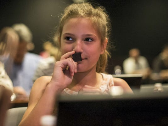 Kinsey Reuwer of Harrisburg smells a piece of chocolate in the latest attraction at Hershey's Chocolate World — the Chocolate Tasting Experience — during the grand opening of the attraction on Wednesday.