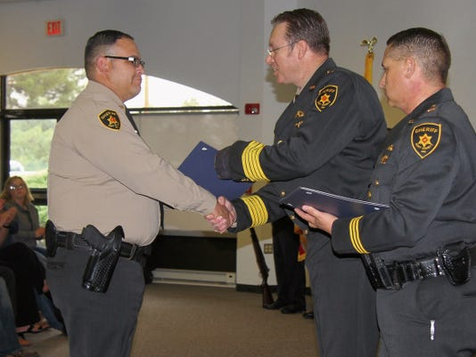 Eddy County Sheriff Scott London presents a meritorious award Tuesday to Deputy Ted Sandoval for his quick thinking that helped rescue a hostage and foil a bank robbery in Artesia in February.