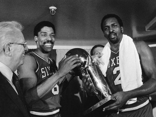 FILE - In this Tuesday, May 31, 1983 file photo, Philadelphia 76ers Julius Erving, left, and Moses Malone, right, hold the NBA Championship trophy after defeating the Los Angeles Lakers in  Los Angeles. Malone, a three-time NBA MVP and one of basketballís most ferocious rebounders, died Sunday, Sept. 13, 2015, according to a The Philadelphia 76ers statement. He was 60. (AP Photo/File)
