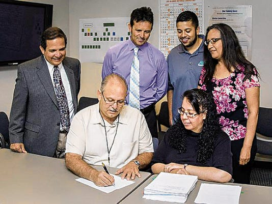 PMI owner Eric Quintana signs a contract with Los Alamos National Labs recently. (Courtesy photo)