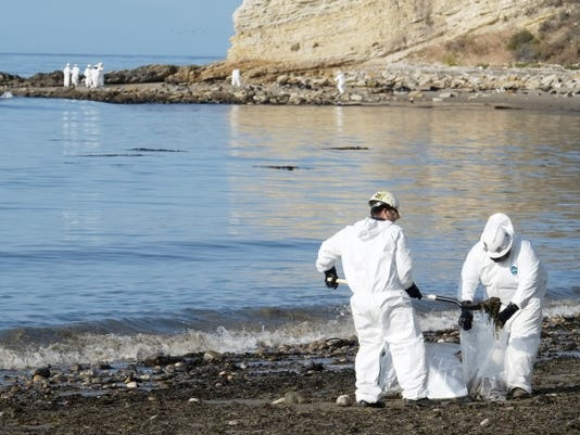 Clean up workers place shovels of oil-laden sand in bags Wednesday while a larger group of workers begin clean up operations at Refugio State Beach, site of an oil spill, north of Goleta, Calif.