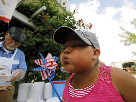 Briyana Biggs blows on her pinwheel Friday during the Family Freedomfest at the Farmington Museum at Gateway Park.