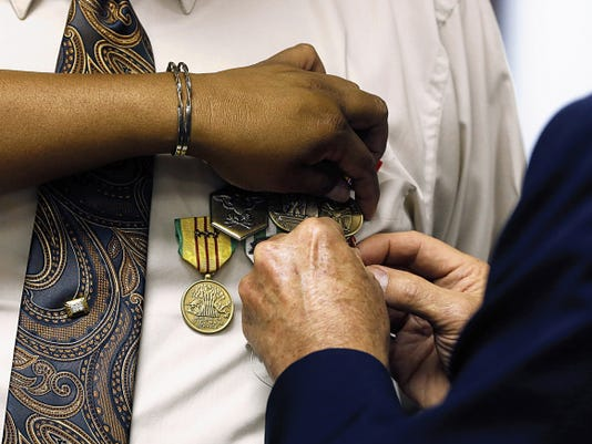 Medals are pinned to the shirt of Army veteran Bob Bass Wednesday at City Hall in Farmington.