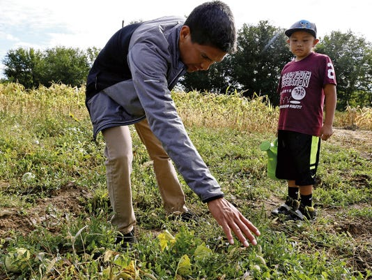 Volunteer Herb Beyale, left, of Shiprock, on Wednesday talks with Aspen Uentillie, 7, of Kirtland, about farming during Dream Diné Charter School's third experiential education day at a farm in Shiprock.