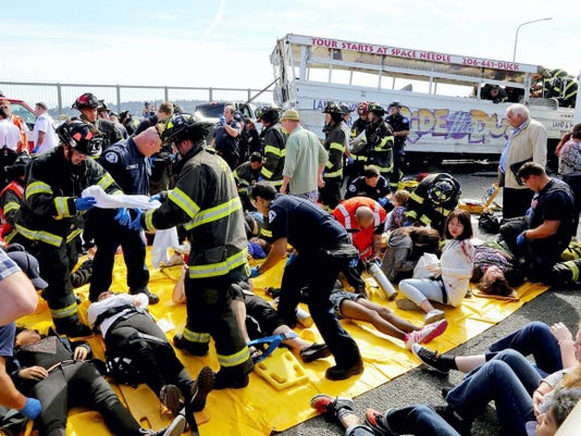 """Emergency personnel work at the scene of a fatal collision involving a charter bus, background, and a """"Ride the Ducks"""" amphibious tour bus, right, on the Aurora Bridge in Seattle on Thursday, Sept. 24, 2015.  (Greg Gilbert/The Seattle Times via AP)"""