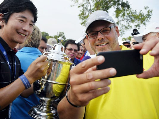 Lancaster Country Club member Chris Simon, right, takes a selfie with the Harton S. Semple trophy on Sunday after the final round of the U.S. Women's Open at Lancaster Country Club. Photo ops such as this have only become possible in recent years as the USGA has lifted restrictions banning cellphones on the Open course.