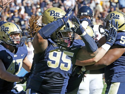 Pittsburgh defensive lineman Khaynin Mosley-Smith (95) celebrates a safety by linebacker Mike Caprara (30) with the rest of the defense in the fourth quarter against Virginia. Pitt won, 29-16.