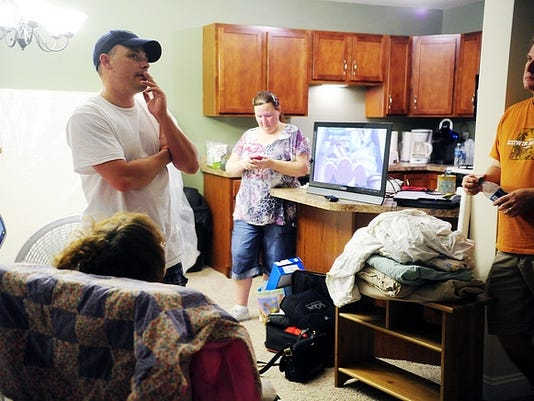 Matt Schwartz, far left, recalls the upcoming examinations and procedures his 8-month-old son Houston will soon go through, as volunteers Shae (center) and David Kokomoor take a break Friday from helping Schwartz unpack a minivan full of overnight necessities that they brought to the Palmyra-area townhouse where Schwartz is relocating. After bringing his 8-month-old baby Houston home from the hospital, Matt Schwartz found that his mother's Springettsbury Township basement where the family has been living was too hot to keep the baby there.