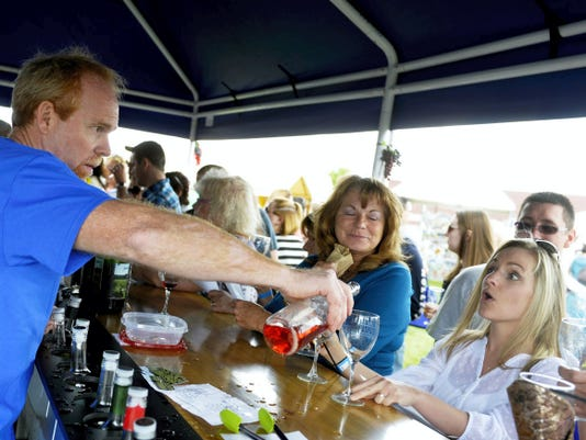 Rusty Heath, left, pours a sample of Jackson Square Vineyards wine for Tamra Boyd of Lancaster at the annual Taste of Pennsylvania Wine and Music Festival last year at the York Expo Center.