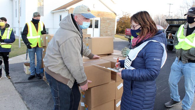 James Wolodkin and Tami Moore spearhead a group of volunteers at the Bankers Baptist Church drive-thru food giveaway Wednesday.
