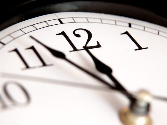 A closeup of hands on an analog clock.