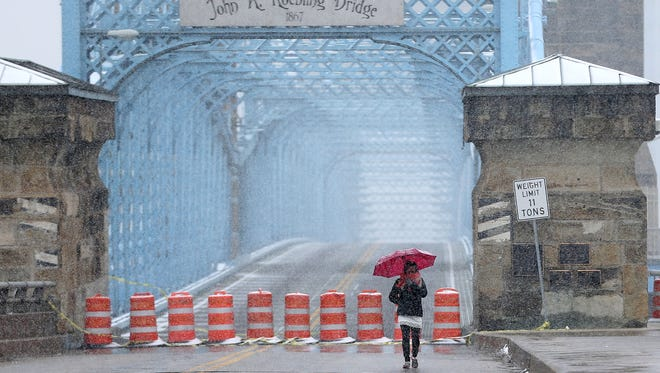 Asha Narayan, visiting from Washington D.C., walks along the John A. Roebling Bridge as snow falls throughout the Cincinnati area, Saturday, March 24, 2018.  A winter weather warning remains in effect until 2 a.m. Sunday for portions of Southeast Indiana, Northeast and Northern Kentucky and Southwest Ohio, including Hamilton County. Butler, Clermont, Brown, and Adams counties are under a winter storm advisory until 2 a.m. Sunday.