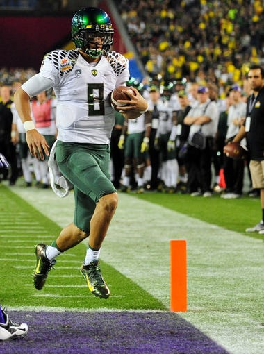 Oregon Ducks quarterback Marcus Mariota (8) scores a 2 yard touchdown during the second half against the Kansas State Wildcats during the Fiesta Bowl at University of Phoenix Stadium. The Ducks beats the Wildcats 35-17.