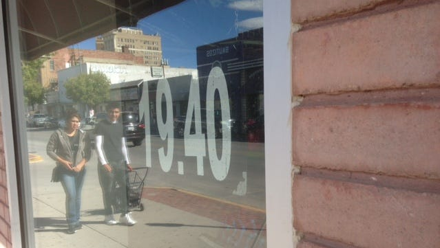 Shoppers are reflected in the window of the Valuta money exchange house in Downtown El Paso, which at one point on Nov. 9, was buying a dollar for 19.40 pesos. It was charging 20.10 pesos to buy a dollar. The peso fell further after Tuesday's presidential election.