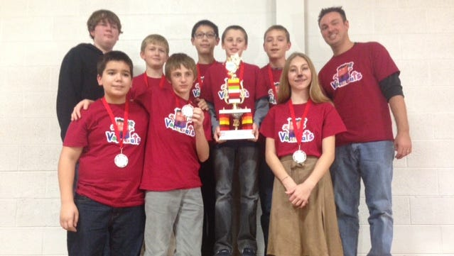 Members of the Vallibots, including science teacher Jason Vallimont, show off their award from regional Lego League competition.