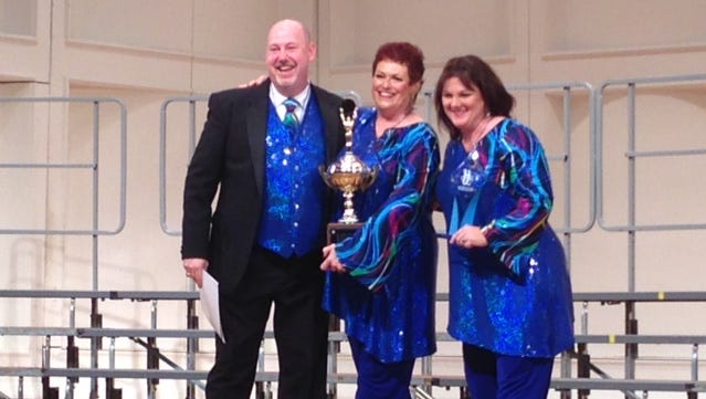 Spirit of the Gulf chorus accepts the trophy for first place at the regionals.