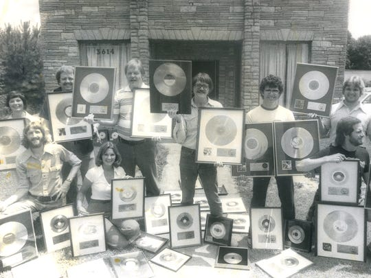 The Swampers studio musicians and staff members pose with gold records outside Muscle Shoals Sound Studio in the 1970s.