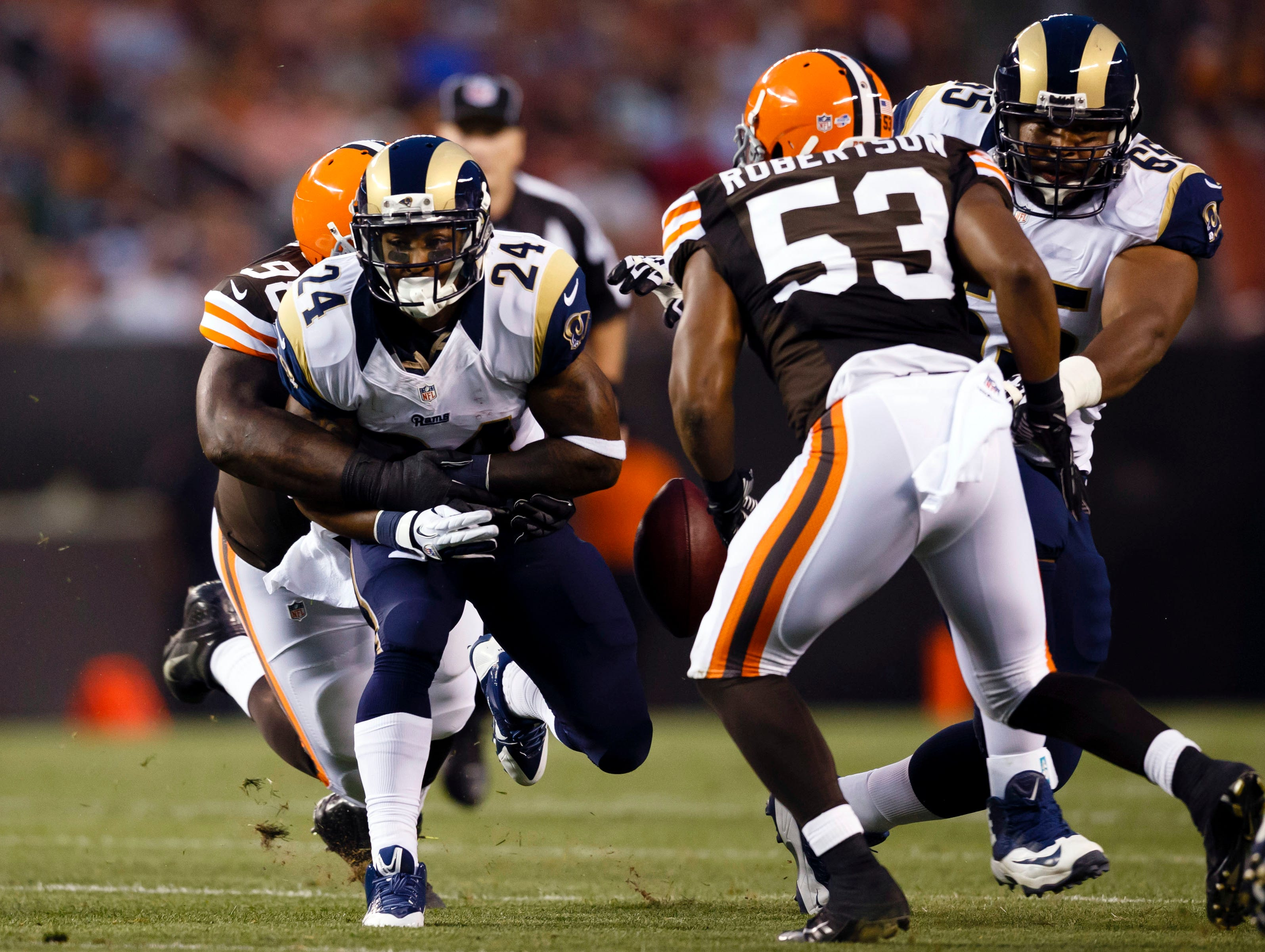 Cleveland Browns defensive tackle Phillip Taylor (98) tries to tackle St. Louis Rams running back Isaiah Pead (24) in the first half at FirstEnergy Stadium.