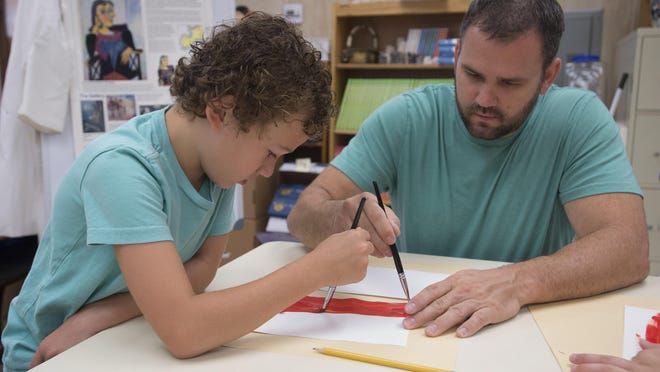 Second-grader, Cameron Green, left, and his father Larry, work together on an art project at Pine Meadow Elementary School Wednesday morning Sept. 30, 2015. Pine Meadow welcomed the Fathers and grandfathers its students to will take their children to school and attend classes with their youngsters.