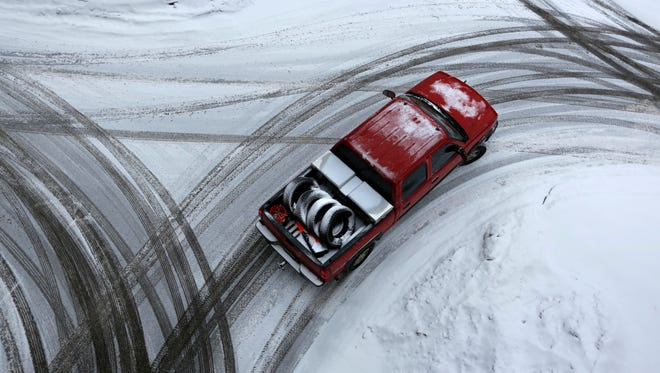 The driver of a pickup appears to have swapped out his general use tires (in the truck's bed) in favor of snow tires just in time to deal with the snow-covered streets in Auburn, Maine, ursday, Dec. 29, 2016.