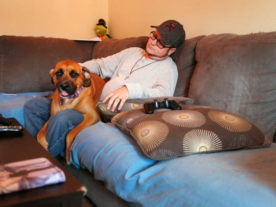 Justin Six, of Springdale, AR., pets his service dog