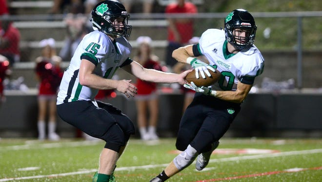 Mountain Heritage's Trey Robinson hands off to Cole Burleson during Friday's 58-31 win at Erwin.