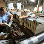 Kylie Frischman, 10, left, her mother Traci, 13-year-old sister Cierra Sjoman, and grandfather Warren Sjoman, all of Marshfield, look through books to buy Sunday during the Marathon County Public Library book sale in Wausau.