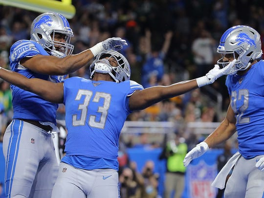 DETROIT, MI - DECEMBER 29: Kerryon Johnson #33 of the Detroit Lions scores a touchdown and celebrates with teammates Jason Cabinda #53 and Logan Thomas #82 during the second quarter of the game against the Green Bay Packers at Ford Field on December 29, 2019 in Detroit, Michigan. (Photo by Leon Halip/Getty Images)