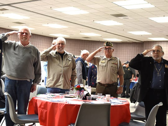 United States' veterans and visitors salute the American Flag at the start of the Nov. 3 gathering at the Novi Civic Center.