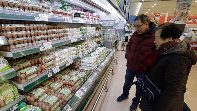 Customers look at eggs at a discount store in Seoul, South Korea, a day after government officials announced that millions of chickens would be culled because of an outbreak of bird flu. Because of the spreading bird flu outbreak, South Korea has asked the United States for the first time to ship it shell eggs.