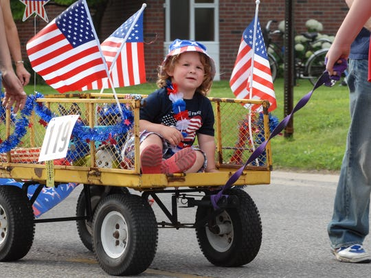 Jackson Walter, of Fraser is surrounded by U.S. flags as he rides in a wagon during the 2013 Pickerel Tournament.