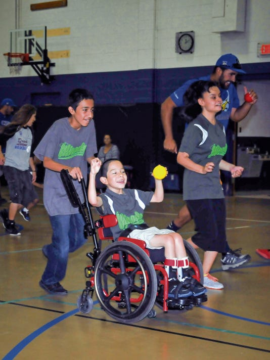 Jett Loe--Sun-News   Eight-year-old Michael Rangel, center, participates in a baseball game at Meerscheidt Recreation Center on Saturday. He and other members of the Meca Miracles, a baseball team for special needs kids, were coached in baseball skills by the Las Cruces Vaqueros.