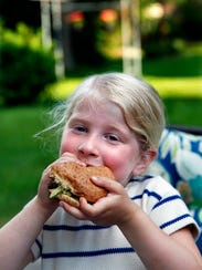 Johanna Adomavich tucks into a black bean burger with