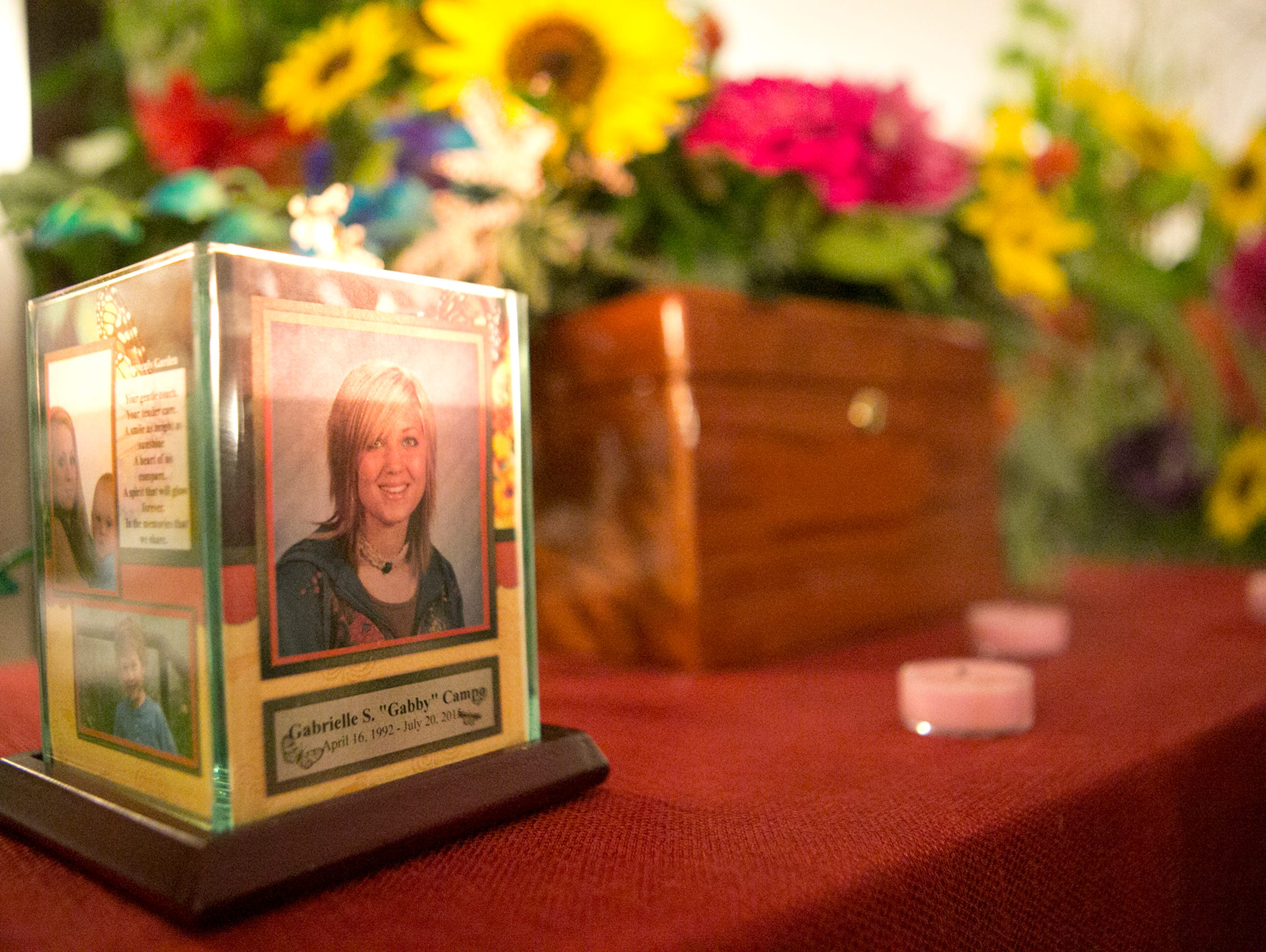 A candle encircled by photos of Gabrielle Campo sits