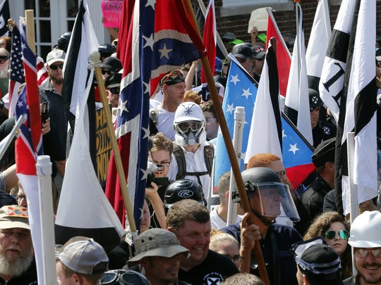 White nationalist demonstrators walk into the entrance of Lee Park surrounded by counter-demonstrators in Charlottesville, Va., on Saturday, Aug. 12.
