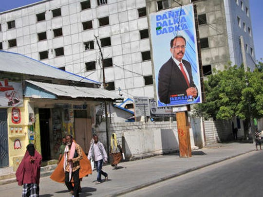 Somalis walk past a campaign poster for candidate Mohamed Abdullahi Farmaajo on the eve of presidential elections in Mogadishu, Somalia Tuesday, Feb. 7, 2017. Graft - vote-buying, fraud, intimidation - is the top concern in a nation that Transparency International now rates as the most corrupt in the world and Mogadishu is in lockdown because of the threat of violence by homegrown Islamic extremist group al-Shabab.