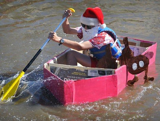 "Elie Lam paddles his boat, ""Summertime Santa"", across"