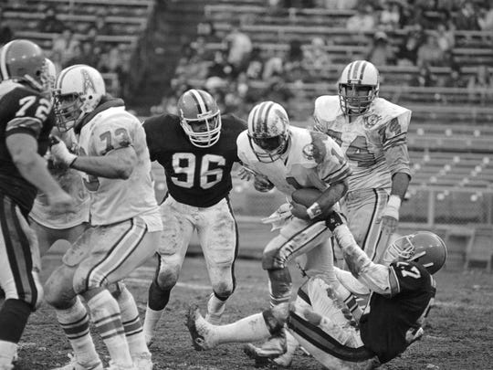 Houston Oilers quarterback Warren Moon (1) is sacked by Cleveland Browns linebacker Clay Matthews (57) while Matthews brother, Oiler tackle Bruce Matthews (74) looks on in a Nov. 26, 1984, game in Cleveland. The Browns won 27-10.