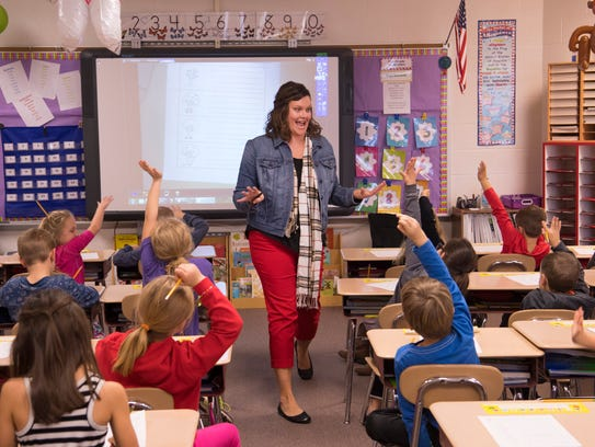 Andrea Boyle's first-graders wave their hands so they