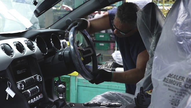A worker installs a Ford Mustang steering wheel on the right side so it can be sold in export markets where people drive on the left. It is made in Flat Rock, Mich.