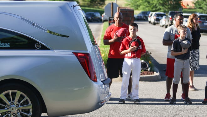 Youth league players line Sango Road in Clarksville and cover their hearts with their hats as Donny Everett's funeral procession passes by on Tuesday.