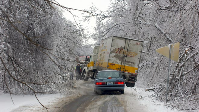 A tow truck assisting a semi-tractor trailer truck on U.S. 60 E near Spottsville, Ky., where it had slipped off the shoulder and was in danger if sliding down a steep embankment. On day two after the ice storm the road was stilled littered with downed limbs and power lines. (Gleaner photo by Mike Lawrence • 831-8346 or mlawrence@thegleaner.com)