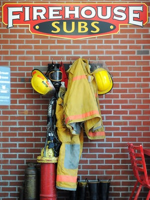 Firefighting equipment hangs on the wall at Firehouse Subs Monday, Aug. 10, 2015, in Sioux Falls.