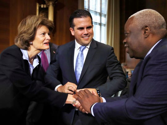 Senate Committee on Energy and Natural Resources Chair Sen. Lisa Murkowski, R-Alaska, left, greets Puerto Rico Gov. Ricardo Rossello, center, and U.S. Virgin Islands Gov. Kenneth Mapp, at a hearing on hurricane recovery, Tuesday, Nov. 14, 2017, on Capitol Hill in Washington. (AP Photo/Jacquelyn Martin)