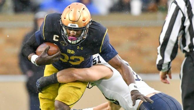 Nov 18, 2017; South Bend, IN, USA; Notre Dame Fighting Irish running back Josh Adams (33) is tackled by Navy Midshipmen linebacker Winn Howard (51) in the first quarter at Notre Dame Stadium. Mandatory Credit: Matt Cashore-USA TODAY Sports