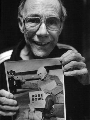 Reporter Edward T. Breslin poses with a Detroit Times photo of him as a hitchhiker to the 1948 Rose Bowl.