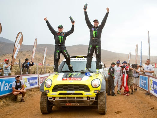 Stage 13: Spain's Nani Roma, right, and co-pilot Michel Perin, of France, celebrate on top of their Mini after winning the car division on Jan. 18. Ten years after winning the motorbikes race in North Africa, Roma became the third man to also win the Dakar Rally in a car.